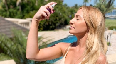 woman spraying butterfly toning mist on her face